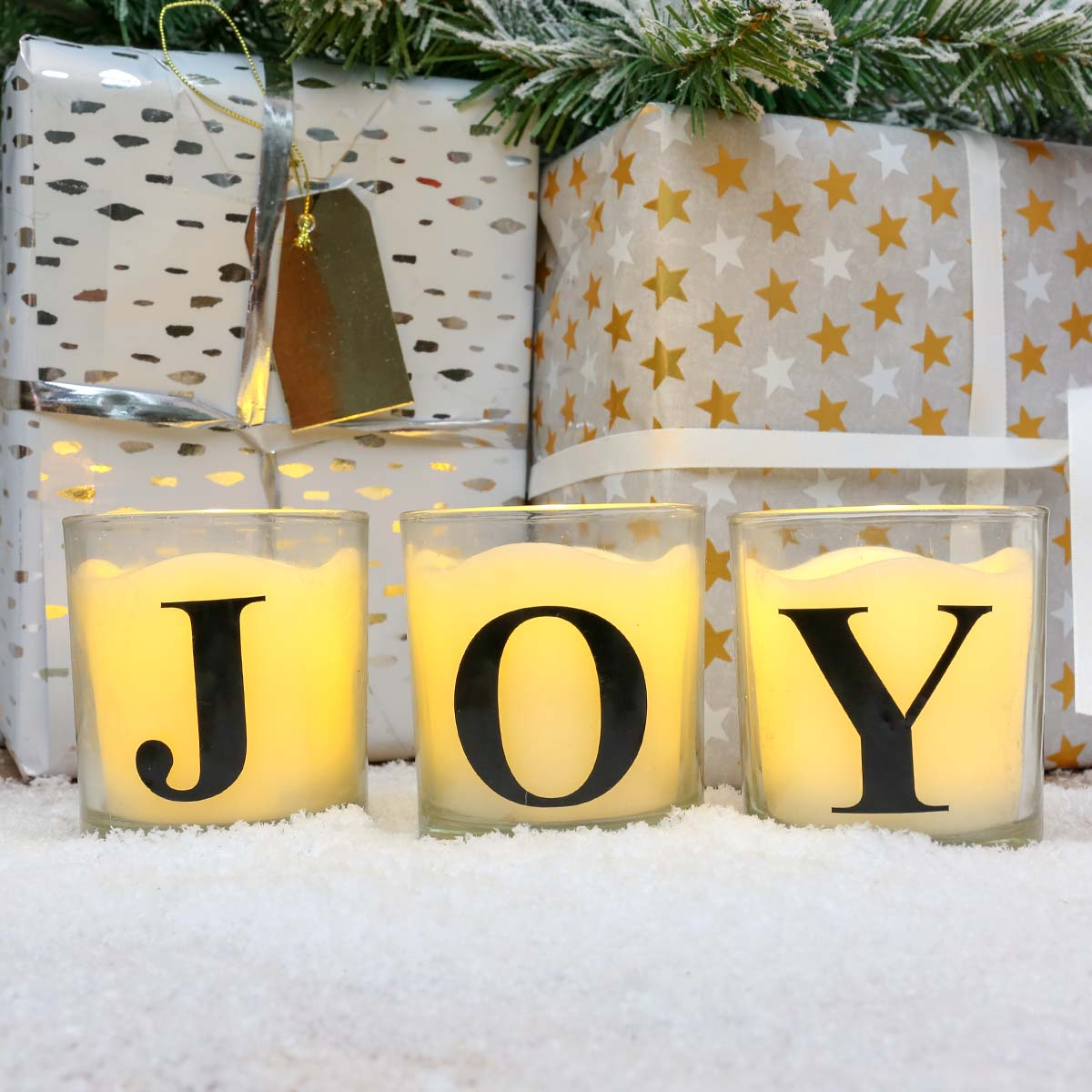 Three battery powered alphabet glass candle jars, with authentic flames, spell the word joy, in front of Christmas presents