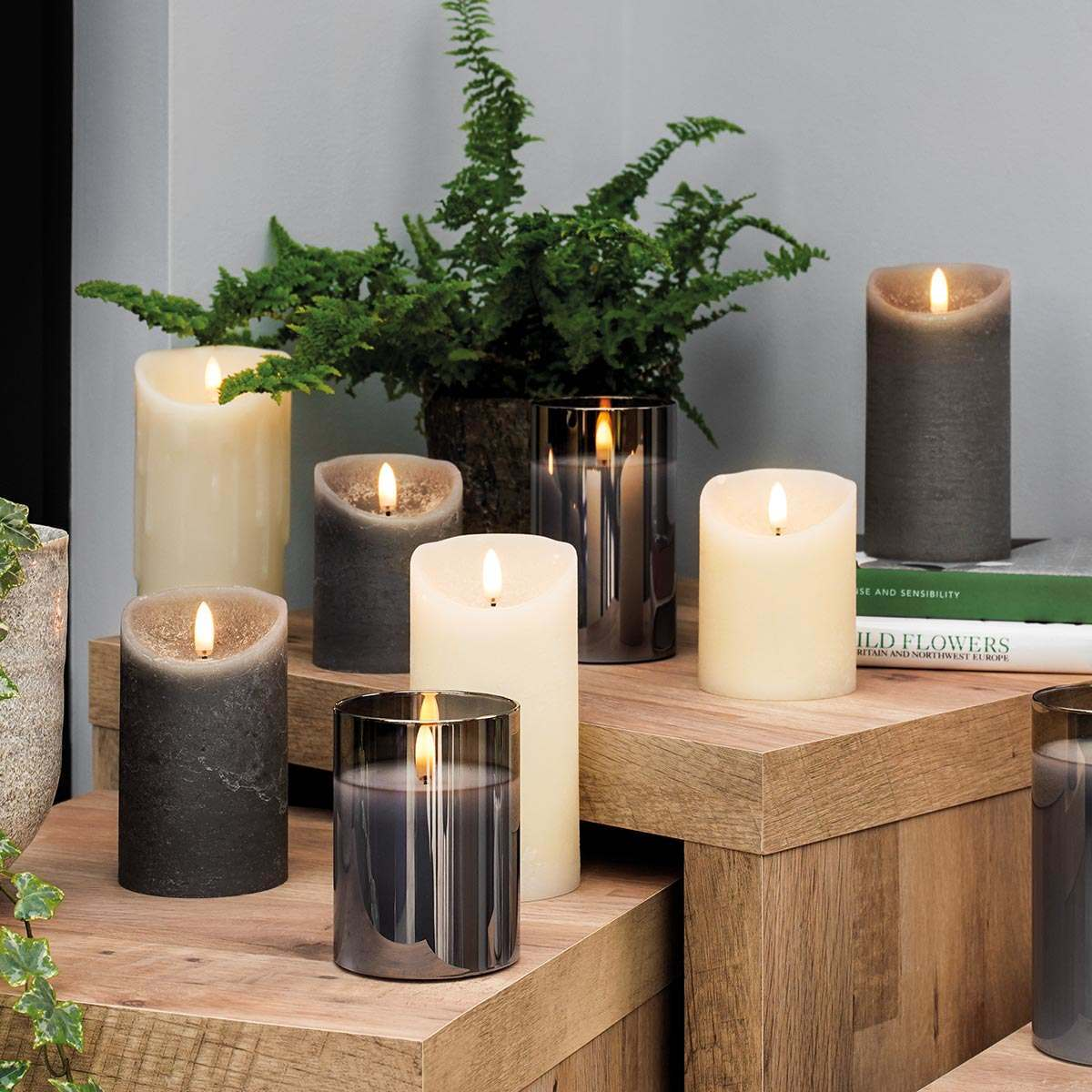 A collection of battery powered authentic flickering flame grey and cream candles, and smoked glass candle jars in the home