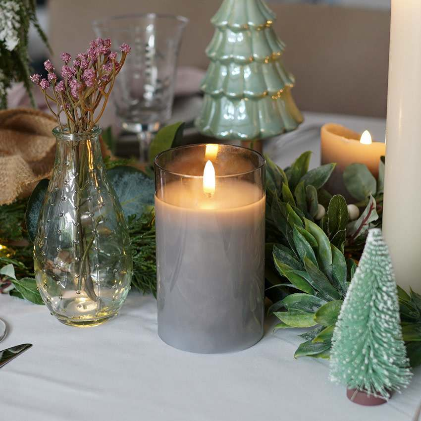 A battery powered smoked glass candle jar with authentic flame being used as Christmas table decoration for a centrepiece