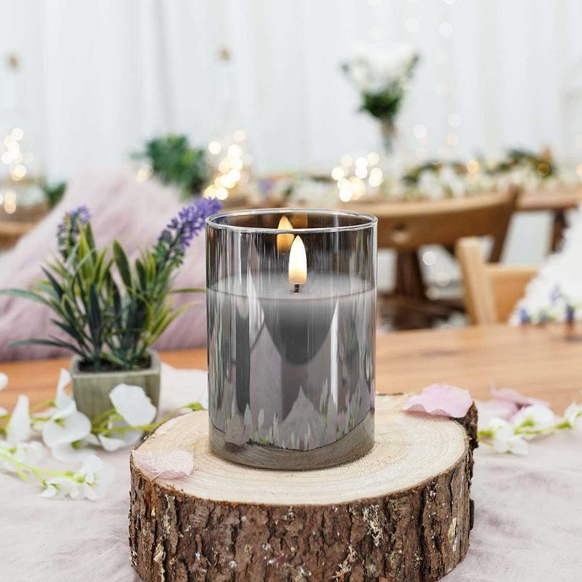 A set of three battery powered smoked glass candle jars, styled on a wooden log as part of a wedding table centrepiece