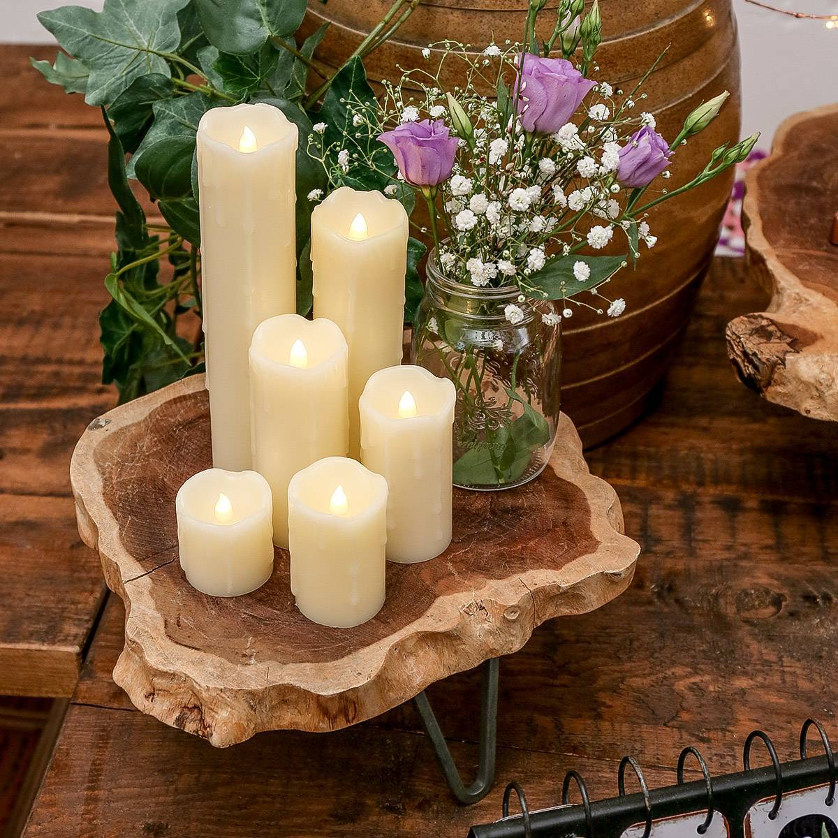 A set of six variously sized cream battery powered LED candles, styled as wedding decoration with flowers