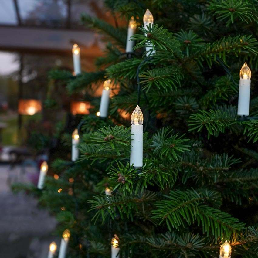 Clip on battery powered candles with warm white flickering LEDs displayed on a Christmas tree
